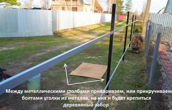 Между металлическими столбами привариваем, или прикручиваем болтами уголки из металла, на них и будет крепиться деревянный забор