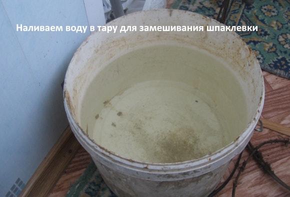 Наливаем воду в тару для замешивания шпаклевки