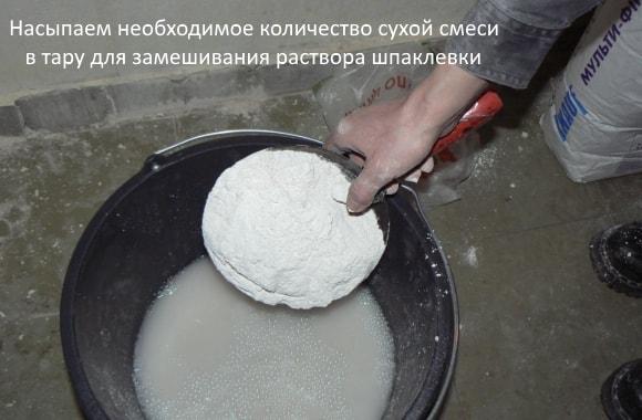 Насыпаем необходимое количество сухой смеси в тару для замешивания раствора шпаклевки